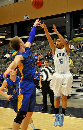 Enid's Donivan Kuhlman shoots over Stillwater 's Jared Dickey Tuesday at the Enid Event Center. (Staff Photo by BILLY HEFTON)