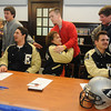 Enid High School Plainsmen football players (seated from left) Stephen Hocker, Sam Clemens and Mason Camp, receive congratulations from family and friends during the national signing day at Enid High School Wednesday, Feb. 5, 2014. (Staff Photo by BONNIE VCULEK)