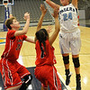 Enid's Grace Enmeir shoots over Lawton defenders  Monday at the Enid Event Center. (Staff Photo by BILLY HEFTON)