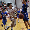 Ringwood's Carlos Aguilar passes the ball around Hunter Lovell of Waukomis Thursday February 2, 2016 at Ringwood HIgh School. (Billy Hefton / Enid News & Eagle)