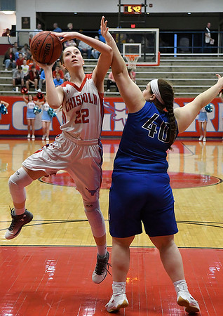 Chisholm's Sunny Middleton shoots around Hennessey's Shay Collins during the district tournament Saturday February 18, 2017 at Chisholm High School. (Billy Hefton / Enid News & Eagle)