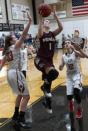 Pioneer's Rylie Schneider drives to the basket between OBA's Brooke Boydstun and Devan Hawk Tuesday February at the OBA gym. (Billy Hefton / Enid News & Eagle)