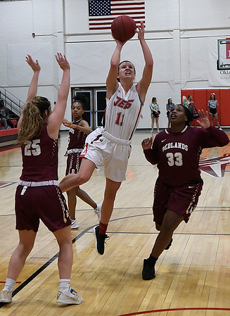 NOC Enid's McKenna Pulley puts up a shot in lane against Redlands' Sydney Newberry and Jania Sheppard Monday February 12, 2018 at the NOC Mabee Center. (Billy Hefton / Enid News & Eagle)