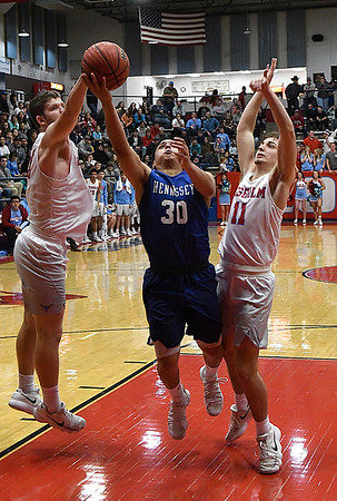 Hennessey's Carlos Rojo puts up a shot between Chisholm's Noah Hann and Cade Balenti during the regional playoffs Friday February 23, 2018 at Chisholm High School. (Billy Hefton / Enid News & Eagle)