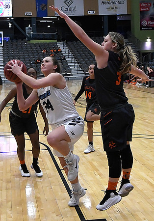 Enid's Elizabeth Plunkett goes under Putnam City's Kelzie Orr for a shot Tuesday February 6, 2018 at the Central National bank Center. (Billy Hefton / Enid News & Eagle)