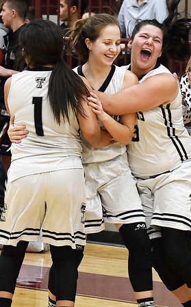 Timberlake's Samantha Phillips (right) and Raegan Scobey (left) hug Jaden Severin after Severin made thw free throws in the final seconds of the game in Timberlake's 51-49 win over Lookeba-Sickles in the regional tournament Thursday February 14, 2019 at Pioneer High School. (Billy Hefton / Enid News & Eagle)