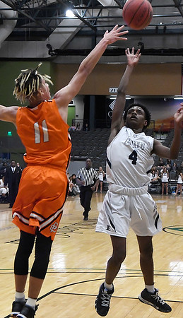 Enid's Carlos Mennefield floats the ball over Putnam City's N'Kozi Harris Tuesday February 12, 2019 at the Central National Bank Center. (Billy Hefton / Enid News & Eagle)