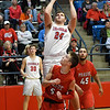 Chisholm's Noah Hann shoots over Prague's Isaac Bloomer during the Longhorn's 53-50 overtime win in a class 3A regional tournament Thursday Feb. 21, 2019 at Chisholm High School. (Billy Hefton / Enid News & Eagle)