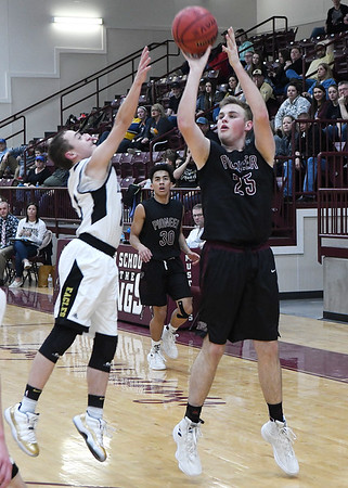 Pioneer's Payton Wingoshoots while defended by Mounds' Devin Stockstill during an elimination game in a class 2A regional tournament Friday Feb. 22, 2019 at Pioneer High School. (Billy Hefton / Enid News & Eagle)