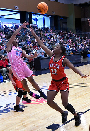 Enid's Mya Edwards makes a pass over Lawton's B.B. Johnson Saturday February 8, 2020 at the Stride Bank Center. (Billy Hefton / Enid News & Eagle)