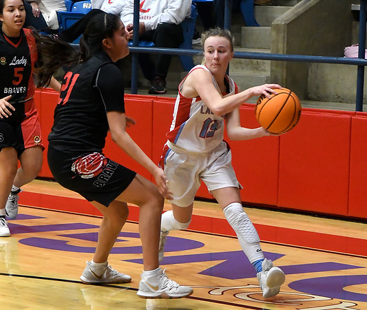 Chisholm's Regi Pasby passes theball around Riverside's Taygen Marshall during a district tournament game at Chisholm High School Saturday, February 22, 2020. (Billy Hefton / Enid News & Eagle)