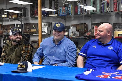 Cooper Wieden sits between his father, Jon Wieden (left) and coach Mark Timberlake (right), after signing a letter of intent Wednesday, February 3, 2021 at Waukoimis High School. (Billy Hefton / Enid News & Eagle)