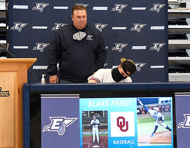 Coach Brad Gore watches as Blake Priest signs a letter of intent during Enid High School's signing day Wednesday, February 3, 2021 at the Enid High School gym. (Billy Hefton / Enid News & Eagle)