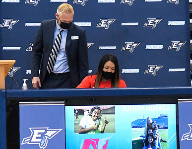 Coach Craig Liddell watches as Judith Huerta signs a letter of intent during Enid High School's signing day Wednesday, February 3, 2021 at the Enid High School gym. (Billy Hefton / Enid News & Eagle)