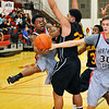 NOC-Enid's david Lewis wraps the ball around Quienton Paras of Redlands  Monday at the NOC Mabee Center. (Staff Photo by BILLY HEFTON)