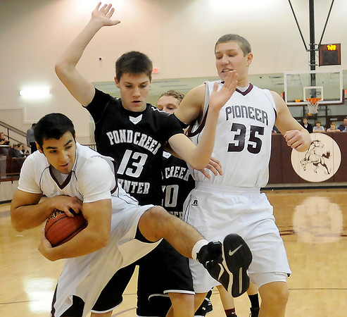 Pioneer's Aaron Chain (left) rebounds against Pond Creek-Hunter's Zach Rayner and T.J. Krittenbrink and teammate, Colby Koontz Friday, Jan. 18, 2013, at Pioneer High School. The Mustangs led 33-27 at the half. (Staff Photo by BONNIE VCULEK)