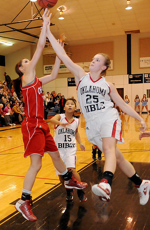 Chisholm's Faith Mirelez and Oklahoma Bible Academy's Kate Anderson collide as Mirelez attempts a bucket Tuesday during the Lady Longhorns' win over the OBA Lady Trojans. (Staff Photo by BONNIE VCULEK)