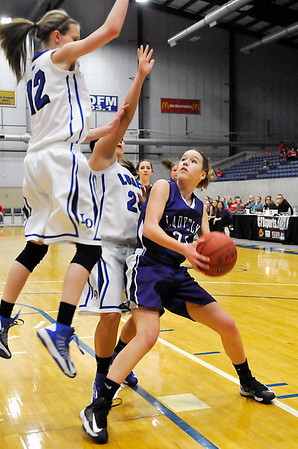Sarah Garvie of Burlington looks for an opening while defended by Lomega's Charity Geis and Amber Clayton during the semi-finals of the Cherokee Strip Conference Tournament January 25, 2013. (Staff Photo by BILLY HEFTON)