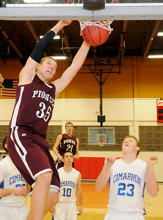 Pioneer's Colby Koontz dunks the ball over three Cimarron Trailblazers Thursday during the opening round of the 89th annual Skeltur Basketball Tournament at the Mabee Center. (Staff Photo by BONNIE VCULEK)