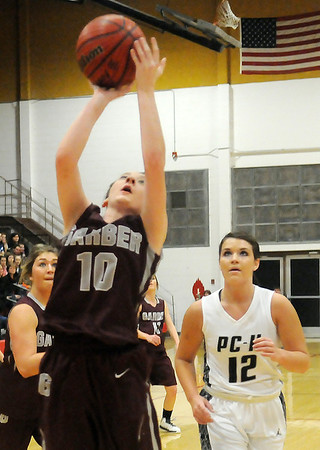 Garber's Shealynn Garrett rebounds and scores in front of Pond Creek-Hunter's KaLanne McKee during the Lady Panthers' 69-48 win over the Lady Wolverines in the 89th annual Skeltur Conference Basketball Tournament Championship at the Mabee Center Saturday, Jan. 26, 2013. (Staff Photo by BONNIE VCULEK)