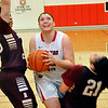 NOC-Enid's Marisha Wallace powers through Redlands defenders Alexis Watson and Kayla Pahcoddy Monday at the NOC Mabee Center. (Staff Photo by BILLY HEFTON)