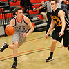 NOC-Enid's Connor Brooks drives the baseline against Redlands Jared Griffin Monday at the NOC Mabee Center. (Staff Photo by BILLY HEFTON)