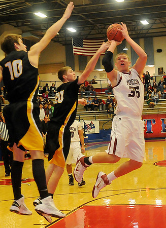 Pioneer's Colby Koontz (right) drives inside for two against Alva's Riley Duncan and Lane Madsen (from left) during the Wheat Capital Basketball Tournament at Chisholm High School Thursday, Jan. 10, 2013. (Staff Photo by BONNIE VCULEK)