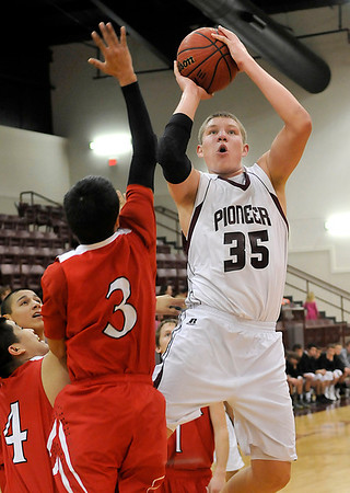 Pioneer's Colby Koontz shoots over Junior Obeso of Dover Tuesday at Pioneer High School. (Staff Photo by BILLY HEFTON)