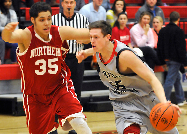 NOC-Enid's Connor Brooks drives toward the basket against Colin Voss of NOC-Tonkawa Monday at the NOC Mabee Center. (Staff Photo by BILLY HEFTON)