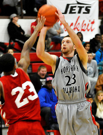NOC-Enid's Dalen Qualls shoots over a NOC-Tonkawa's Matt Brasser during a game earlier this season. (Staff Photo by BILLY HEFTON)