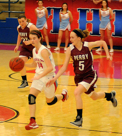 Chisholm's Megan Galusha brings the ball up the court as Perry's Shauni Edwards defends Thursday, Jan. 10, 2013, during the Wheat Capital Basketball Tournament at Chisholm High School. (Staff Photo by BONNIE VCULEK)