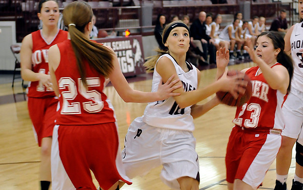 Pioneer's Shelby Flavell drives toward the basket between Dover's Alex Beck and Emily Mathews Tuesday at Pioneer High School. (Staff Photo by BILLY HEFTON)