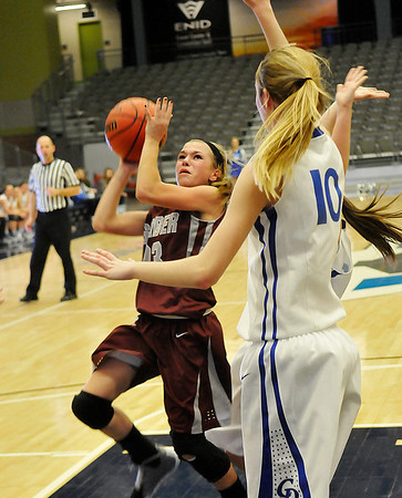 Garber's Halie Schovanec drives through the lane against Jessi Parsons of Covington-Douglas Friday at the Enid Event Center during the 3rd place game of the 90th Skeltur Conference Tournament. (Staff Photo by BILLY HEFTON)