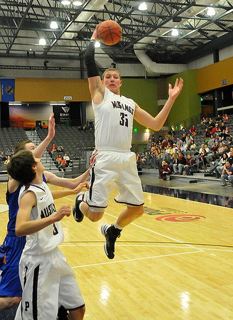 Pioneer's Colby Koontz leaps for a rebound against Drummond Saturday at the Enid Event Center during the finals of the 90th Skeltur Conference Tournament. (Staff Photo by BILLY HEFTON)