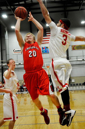 Cherokee's Tanner Bowman drives through the lane against Andre Lizar of Kremlin-Hillsdale Firday at the Chisholn Trail Expo Center during a semi-final game of the Cherokee Strip Conference Tournament. (Staff Photo by BILLY HEFTON
