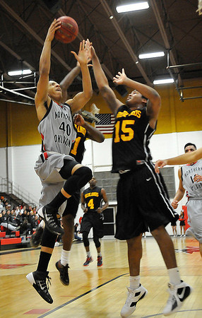 NOC Enid's Josh Palmer goes to the basket against Redlands' Zarif Basil Monday at the NOC Mabee Center. (Staff Photo by BILLY HEFTON)
