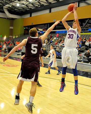 Chance Mullins of Waukomis shoots over Garber's Alec Monsees at the Enid Event Center Wednesday during the 90th Skeltur Conference Tournament. (Staff Photo by BILLY HEFTON)