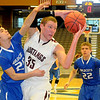 Pioneer's Colby Koontz controls an offensive rebound against Covington-Douglas's Tyler Hamlett (25) and Cody Taylor (22) during the Mustangs 37-9 win in the Skeltur Conference Basketball Tournament at the Enid Event Center Monday, Jan. 20, 2014. (Staff Photo by BONNIE VCULEK)