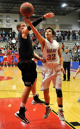 Chisholm's Danner Kiernan goes under the arm of Pioneer's Colby Koontz to score a basket Thursday during the first round of the Wheat Capital Basketball Tournament at Chisholm High School. (Staff Photo by BILLY HEFTON)