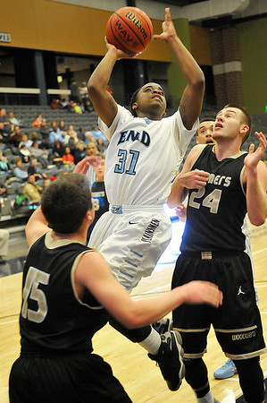 Enid's Marcus Moore leaps toward the basket against Woodward's Garrett Owen and Ty Richey Tuesday at the Enid Event Center. (Staff Photo by BILLY HEFTON)