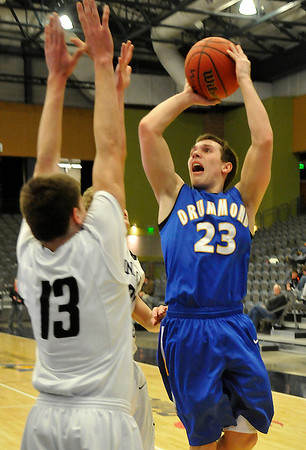 Drummond's Parker Jankey shoots over Zach Rayner of Pond Creek-Hunter Thursday at the Enid Event Center during a semi-final game of the 90th Skeltur Conference Tournament. (Staff Photo by BILLY HEFTON)