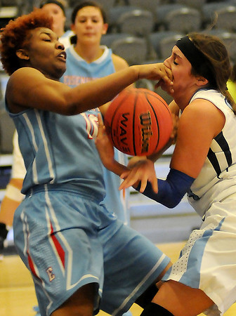 Enid's Grace Enmeier survives a fist to the face from Lawton Eisenhower's Nikki Smith as they battle for the ball during the Lady Eagles' 33-32 win over the Pacers at the Enid Event Center Saturday, Jan. 18, 2014. (Staff Photo by BONNIE VCULEK)