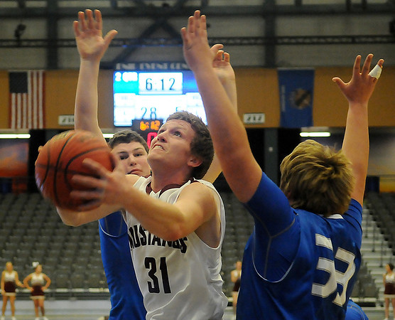 Pioneer's Patrick Williams splits two Covington-Douglas defenders as he scores two for the Mustangs during the 90th annual Skeltur Conference Basketball Tournament at the Enid Event Center Monday, Jan. 20, 2014. (Staff Photo by BONNIE VCULEK)