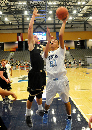 Enid's Randy Porter puts up a shot against Woodward's Kaleb Roach Tuesday at the Enid Event Center. (Staff Photo by BILLY HEFTON)