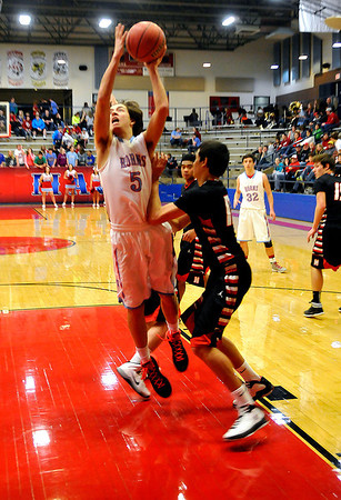 Chisholm's Bryson Rolfe is fouled by Morrison's Ty Stout as he puts up a shot Tuesday at Chisholm High School. (Staff Photo by BILLY HEFTON)