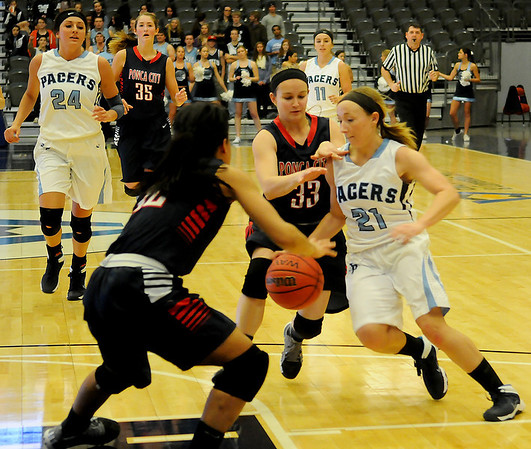 Enid's Shelley Mueller (21) controls the ball as she dribbles between two Ponca City defenders at the Enid Event Center Friday, Jan. 17, 2014. Grace Enmeier (24), Abby Lee (11) and Mueller are the only seniors on the Pacers' basketball team. (Staff Photo by BONNIE VCULEK)