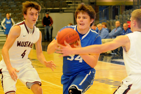Covington-Douglas's Dylan Daugherty drives inside against Pioneer's Brandon McNaughton (left) and Kade Cronkhite (right) during the Skeltur Conference Basketball Tournament at the Enid Event Center Monday, Jan. 20, 2014. (Staff Photo by BONNIE VCULEK)
