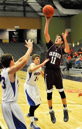 Garber's Parker Betchen shoots over Aaron Harrington and Hunter Lovell of Waukomis at the Enid Event Center Wednesday during the 90th Skeltur Conference Tournament. (Staff Photo by BILLY HEFTON)