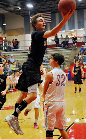 Pioneer's Brandon McNaughton jumps around Chisholm's Danner Kiernan Thursday during the first round of the Wheat Capital Basketball Tournament at Chisholm High School. (Staff Photo by BILLY HEFTON)