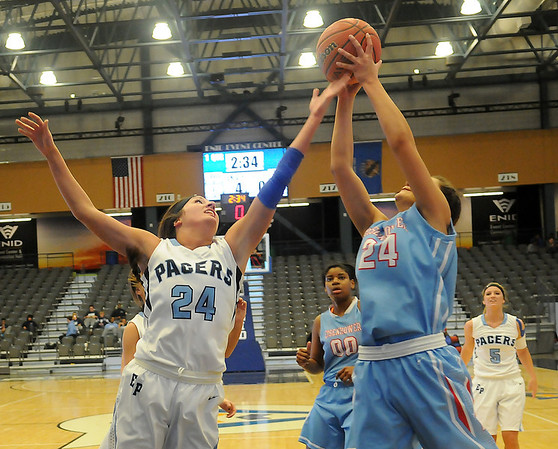 Enid's Grace Enmeier and Lawton Eisenhower's Kennedi Simien battle for an offensive board at the Enid Event Center Saturday, Jan. 18, 2014. (Staff Photo by BONNIE VCULEK)